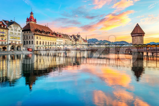 Historical wooden Chapel bridge and the Old town of Lucerne, Switzerland, reflecting in Reuss river on dramatical sunrise