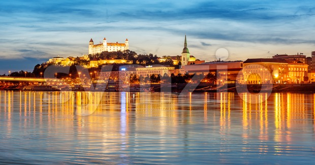 Panoramic view of the Bratislava Old town reflecting in Danube river on sunset, Slovakia