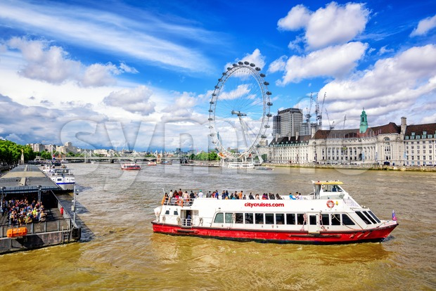 London, UK - 23 July 2017: Cruise tour boat departs from a pier on Thames river in front of London ...