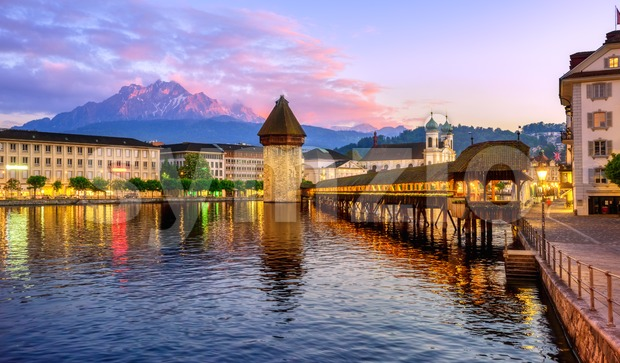 Lucerne city, Switzerland, view of Mount Pilatus, wooden Chapel bridge, the Water Tower and Old town on dramatical sunset