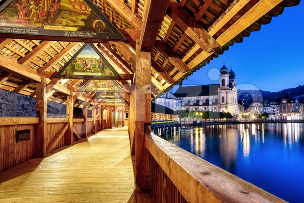 Lucerne city, Switzerland, view of Jesuit church from historical wooden Chapel Bridge, famous for its medieval paintings dating back to ...
