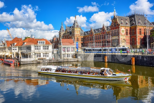 Amsterdam, Netherlands - 12 July 2020: Tourist boat and a tram in front of the Amsterdam Centraal train station, the ...