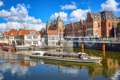 Tourist boat in front of the central train station in Amsterdam city, Netherlands Stock Photo