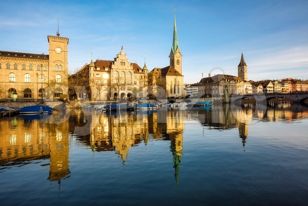 Zurich city's historical Old town center with the Town Hall, Fraumunster and St Peter churches reflecting in Limmat river in ...